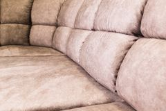 Close-up of an expensive soft textile sofa of beige color with brown shades. Interior Background royalty free stock photos