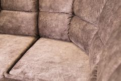 Close-up of an expensive soft textile sofa of beige color with brown shades. Interior Background royalty free stock photography