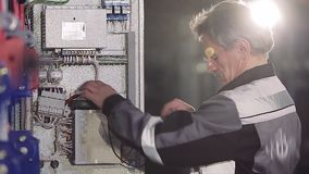 Close-up of experienced man working with electric meter.