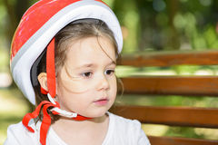 Close-up of a expressive little girl with colorful red safety helmet Royalty Free Stock Image