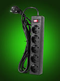 Close up of extension power strip on a green background Royalty Free Stock Image