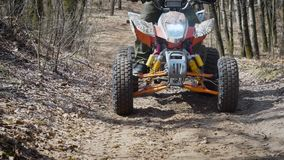 Close up of a extreme rider in green protective equipment and helmet is operating ATV and moving along the road in the stock video footage