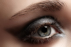 Close-up eye with dark gray eyeshadow stock images