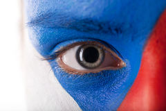 Close up of eye with dilated pupil. Face is painted in blue, red and white colors Royalty Free Stock Image
