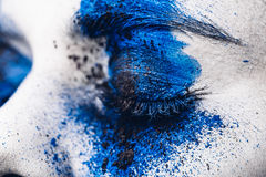 Close up eye of fashion model girl with colorful powder make up. Beauty woman with bright blue makeup and white skin. Royalty Free Stock Image