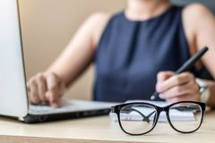 Close up eye glasses with Businesswoman using laptop analysis marketing plan background. Business, Finance and Vision concepts stock image