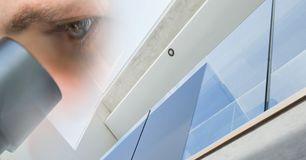 Close up of eye looking in microscope with window transition Royalty Free Stock Images
