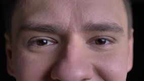 Close-up eye-portrait of middle-aged caucasian man smiling into camera on black background. stock video