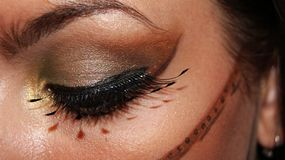 Close up of an eye tribal inspiration professional make up in gold, brown and black color with fantasy false lashes stock images