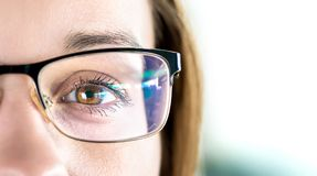 Close up of eye and woman wearing glasses. Optometry, myopia or laser surgery concept. Brown eyed girl with spectacles. royalty free stock image