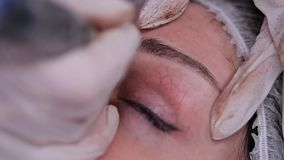 Close-up eyebrow feathering. Technique of applying permanent makeup. 4K Slow Mo. Close-up eyebrow feathering. Technique of applying permanent makeup stock video footage