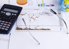 Eyeglass on Stock chart and calculator for finance concept. Close up of Eyeglass on Stock chart and calculator for finance concept royalty free stock image