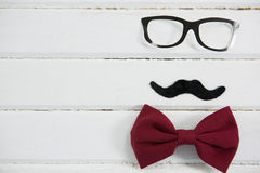 Close up of eyeglasses and bow tie arranged with mustache on table Royalty Free Stock Photo