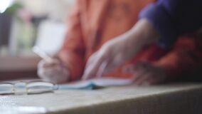 Close-up of eyeglasses lying on the table as blurred Caucasian little boy sitting at the table with pencil. Village. Child doing homework indoors. Education stock footage