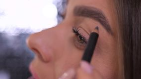 Close up. Eyes, eyebrows. The girl paints an eyebrow shape with a pencil. 4K Slow Mo. Close up. Eyes, eyebrows. The girl paints an eyebrow shape with a pencil stock video