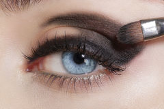 Close up on eyes , making colorful eyeshadows and eyeliner Stock Image