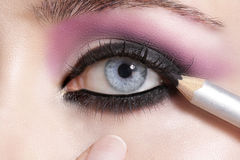Close up on eyes , making colorful eyeshadows and eyeliner Royalty Free Stock Photo