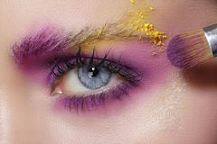 Close up on eyes , making colorful eyeshadows and eyeliner Royalty Free Stock Images