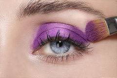 Close up on eyes , making colorful eyeshadows and eyeliner Stock Photos