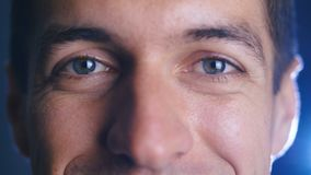 Close up eyes of young happy man looking into camera lens. Close-up of a male eyes. stock video footage