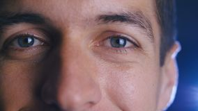 Close up eyes of young happy man looking into camera lens. Close-up of a male eyes. stock footage