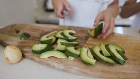 Close-up A faca corta o abacate maduro em fatias As mãos fêmeas com faca estão cortando o abacate verde na placa de corte de made video estoque