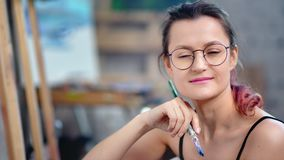 Close-up face of adorable casual female skilled painter posing at workshop holding paintbrush stock video footage