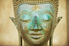 Close up of a face of an ancient copper Buddha statue outside of the Hor Phra Keo temple in Vientiane, Laos. Close up of a face of an ancient copper Buddha royalty free stock photography