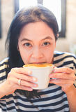 Close up face of asian woman sip hot cappuccino coffee in cafe s Royalty Free Stock Image