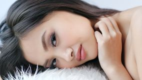 Close-up face of attractive Asian woman flirting and relaxing putting her head on white fluffy fur stock video