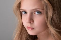 Nice child is expressing thoughtfulness. Close-up of face of attractive little girl is standing and looking at camera seriously. Focus on her big kind eyes Stock Photos
