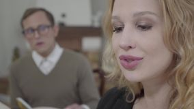 Close up face of beautiful blond woman reading aloud the book in the foreground while modestly dressed man looking at. Close-up face of a beautiful blond woman stock footage