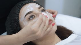 Close up face of beautiful girl does cosmetic procedure in beauty salon, slow motion