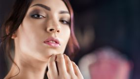 Close-up face of beautiful Hispanic young woman with perfect skin and evening makeup. Portrait of attractive young brunette girl posing relaxing and looking at stock video