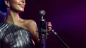 Close up face of beautiful singing girl curly afro hair singer sing with microphone karaoke song. On stage on dark background royalty free stock image
