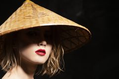 Close-up face of a beautiful young blonde girl with red lips and eyes hidden in the shadow of a cone-shaped Asian cane hat. Clean. Healthy skin. Fashionable stock photo