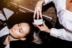 Close up face of beautiful young smiling woman getting hair care procedures in beauty salon, her eyes are closed with relaxation. stock photo