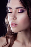 Close-up face, bright eye shadow, makeup. Shallow depth of field, black background Royalty Free Stock Photography