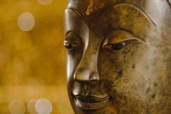 Close up face on buddha head statue with Bokeh background Royalty Free Stock Photography