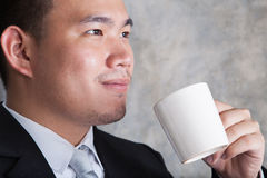 Close up face of business man and ceramic coffee cup in hand wit. H happiness emotion in eyes Stock Photography