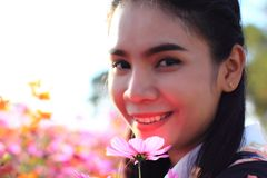 Close up face,caucasian woman and expression happiness,pretty girl with pink cosmos flowers stock photography