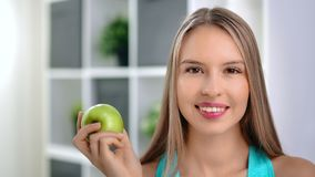 Close-up face of charming vegetarian girl smiling posing with green vitamin apple looking at camera