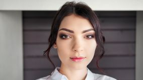 Close-up face of confident Caucasian stylish woman with perfect makeup looking at camera. Portrait of adorable young brunette girl posing indoor stock video
