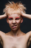 Close up on face of crazy mad cocky young woman with stylish dyed pink hair, hands ruffle her haircut angry and bold Royalty Free Stock Photos