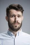 Close up face of  discouraged man. Close up of face of discouraged man on gray background Royalty Free Stock Photography