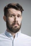Close up face of  discouraged man. Close up of face of discouraged man on gray background Stock Photos