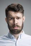 Close up face of  discouraged man. Close up of face of discouraged man on gray background Stock Photography