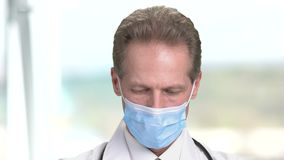 Close up face of a doctor in mask looks down. Serious physician with medical mask. Abstract blurred background in bright room in hospital stock video