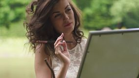 Close-up face of dreamy brunette curled woman artist with pencil in hands painting the picture outdoor in the forest. Close-up of beautiful dreamy brunette woman stock video footage