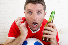 Close up face fan man watching football on tv in team jersey suffering nervous. Close up face of young fan man watching football game on television wearing team Royalty Free Stock Image
